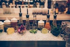 Ingredientes y jarabes para los cócteles en el contador de la barra en el club nocturno foto de archivo