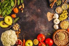 Ingredienti alimentari del vegano su un fondo scuro Verdure, frutti, immagine stock