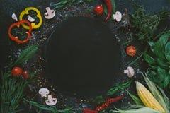 Ingredienti alimentari e spezie per la cottura della pizza Posto vuoto rotondo per pizza o il vostro testo Funghi, pomodori, form immagini stock