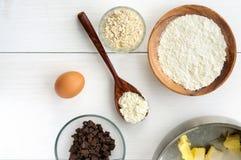 Ingredienti alimentari ed utensili della cucina per la cottura dei biscotti dell'avena su fondo di legno bianco Vista piana super Fotografia Stock
