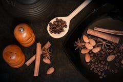 Ingredienti alimentari per cucinare Anice stellato, bastoni di cannella, mandorle su un fondo nero Immagine Stock Libera da Diritti