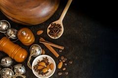 Ingredienti alimentari per cucinare Anice stellato, bastoni di cannella, mandorle su un fondo nero Immagini Stock