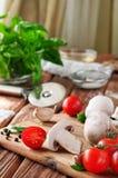 Ingredienti alimentari per i piatti della pasta o della pizza su una tavola di legno nella cucina rustica Immagine Stock