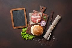 Ingredienti cotoletta, lattuga, panino, cetrioli e cipolla crudi dell'hamburger su fondo arrugginito immagini stock libere da diritti