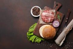 Ingredienti cotoletta, lattuga, panino, cetrioli e cipolla crudi dell'hamburger su fondo arrugginito immagine stock libera da diritti