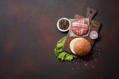 Ingredienti cotoletta, lattuga, panino, formaggio, cetrioli e cipolla crudi dell'hamburger su fondo arrugginito fotografia stock libera da diritti