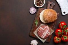 Ingredienti cotoletta, pomodori, lattuga, panino, formaggio, cetrioli e cipolla crudi dell'hamburger su fondo arrugginito immagine stock