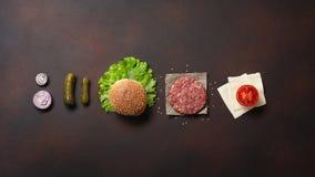 Ingredienti cotoletta, pomodori, lattuga, panino, formaggio, cetrioli e cipolla crudi dell'hamburger su fondo arrugginito immagini stock libere da diritti