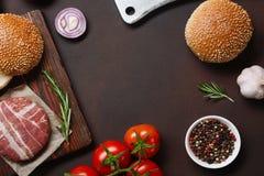 Ingredienti cotoletta, pomodori, lattuga, panino, formaggio, cetrioli e cipolla crudi dell'hamburger su fondo arrugginito fotografie stock libere da diritti