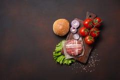 Ingredienti cotoletta, pomodori, lattuga, panino, formaggio, cetrioli e cipolla crudi dell'hamburger su fondo arrugginito fotografie stock
