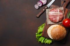 Ingredienti cotoletta, pomodori, lattuga, panino, formaggio, cetrioli e cipolla crudi dell'hamburger su fondo arrugginito fotografia stock
