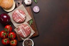 Ingredienti cotoletta, pomodori, lattuga, panino, formaggio, cetrioli e cipolla crudi dell'hamburger su fondo arrugginito fotografia stock libera da diritti
