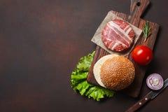 Ingredienti cotoletta, pomodori, lattuga, panino, formaggio, cetrioli e cipolla crudi dell'hamburger su fondo arrugginito immagini stock