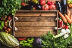Ingredienti crudi freschi per la cottura sana o insalata che fa con il vassoio di legno rustico nel centro, vista superiore, spaz Immagini Stock Libere da Diritti