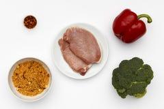 Ingredienti crudi per una ciotola di carne di maiale e di cuscus deliziosi di scatto con le verdure e le spezie fotografie stock
