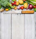 Ingredienti degli ortaggi freschi per la cottura con il coltello da cucina utilizzato su fondo di legno bianco, vista superiore,  Immagine Stock