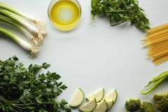 Ingredienti degli spaghetti: verdure verdi, olio d'oliva, prezzemolo, cipolla, broccoli, zucchini, paprica Fotografia Stock