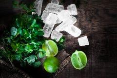 Ingredienti del cocktail di Mojito - la menta fresca, calce, ghiaccia di legno Immagine Stock