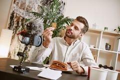 Ingredienti del panino Ritratto del blogger barbuto maschio che assaggia un alimento mentre registrando nuovo video per il suo vl fotografia stock