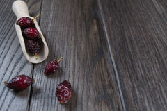 Ingredienti del tè delle rose dell'anca sulla tavola in cucchiaio di legno Fotografia Stock