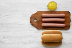 Ingredienti dell'hot dog: salsiccie sul bordo di legno, sui panini di hot dog e sulla senape su superficie di legno bianca, vista fotografia stock