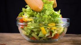 Ingredienti dell'insalata di miscelazione in ciotola di vetro stock footage