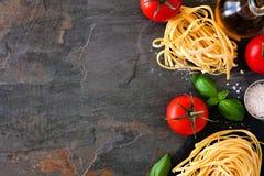 Ingredienti della pasta, sopra il confine del lato di vista contro un fondo dell'ardesia immagini stock