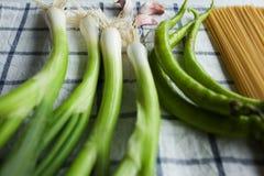Ingredienti della pasta sull'asciugamano bianco: cipolla, aglio, paprica Immagini Stock