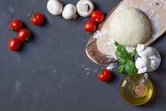 Ingredienti della pizza sui precedenti grigi con lo spazio della copia, pasta, pomodori, funghi, basilico, mozzarella, olio d'oli immagine stock