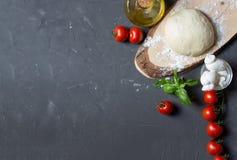 Ingredienti della pizza sui precedenti grigi con lo spazio della copia, potete mettere la vostra immagine o iscrizione a sinistra fotografie stock