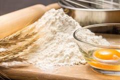 Ingredienti di cottura con le orecchie del grano a bordo Fotografie Stock