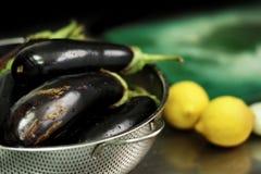 Ingredienti di cucina del vegano e del Greco Melanzana e limoni Fotografia Stock