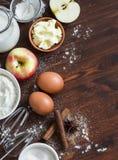 Ingredienti e strumenti per cuocere - farina, uova, burro, mele, cannella Fotografia Stock