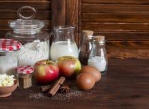 Ingredienti e strumenti per cuocere - farina, uova, burro, mele, cannella su una superficie di legno rustica marrone Immagine Stock
