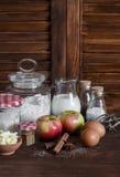 Ingredienti e strumenti per cuocere - farina, uova, burro, mele, cannella su una superficie di legno rustica marrone Immagini Stock Libere da Diritti