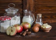 Ingredienti e strumenti per cuocere - farina, uova, burro, mele, cannella su una superficie di legno rustica marrone Fotografia Stock Libera da Diritti