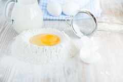 Ingredienti e strumenti per cuocere - farina, uova e bicchiere di latte sui precedenti rustici di legno della tavola, fuoco selet Fotografia Stock