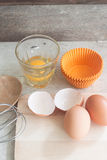 Ingredienti e strumenti per fare un dolce, uova, tazze del forno Fotografia Stock