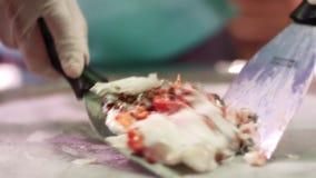 Ingredienti mescolantesi del cuoco unico per la cottura del rotolo del gelato Latte mescolantesi e frutti stock footage