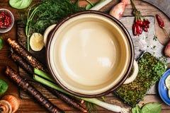 Ingredienti organici freschi delle verdure per la cottura saporita intorno alla pentola di cottura vuota, vista superiore Fotografia Stock