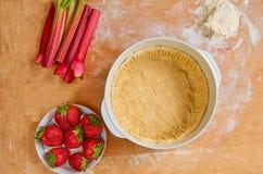 Ingredienti per acido vegetariano - fragole organiche, rabarbaro affettato e pasta cruda nel piatto bollente fotografie stock