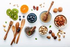 Ingredienti per alimenti sani fondo, dadi, miele, bacche Immagini Stock