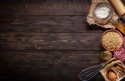 Ingredienti per cuocere sul fondo di legno scuro vuoto Fotografia Stock