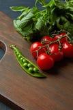 Ingredienti per i pani tostati con la pasta ed i pomodori del basilico-pisello su un bordo di legno Immagine Stock