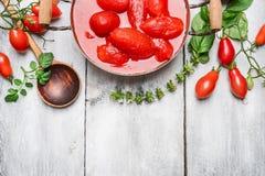 Ingredienti per i pomodori della salsa al pomodoro -, il basilico ed il cucchiaio freschi e sbucciati su fondo di legno bianco, v Immagini Stock Libere da Diritti