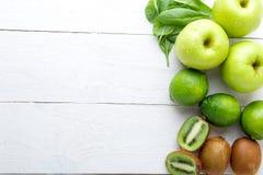 Ingredienti per il frullato Frutti verdi su fondo di legno bianco Apple, calce, spinaci, kiwi detox Alimento sano Vista superiore Immagine Stock
