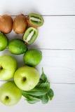 Ingredienti per il frullato Frutti verdi su fondo di legno bianco Apple, calce, spinaci, kiwi detox Alimento sano Vista superiore Immagini Stock