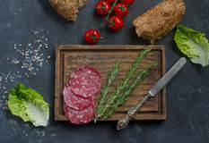 Ingredienti per il panino, il pane, i pomodori, la salsiccia ed il coltello dell'annata su un bordo di legno e su un fondo scuro, Immagini Stock Libere da Diritti