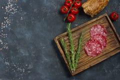 Ingredienti per il panino, il pane, i pomodori, la salsiccia ed il coltello dell'annata su un bordo di legno e su un fondo scuro, Immagini Stock