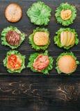 Ingredienti per l'hamburger Nove hamburger nelle fasi differenti di prontezza Vista da sopra Priorità bassa di legno nera Fotografia Stock